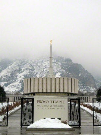 A front view of the Provo Utah Temple on a gray winter day, with the temple's sign on the black fence and the gates open leading to the temple.