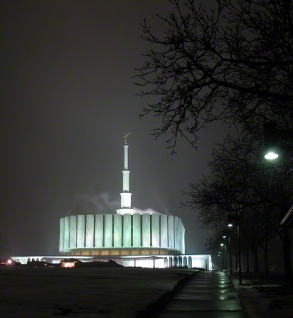The Provo Utah Temple on a winter night, seen from the bottom of the hill, with the silhouette of a large bare tree on the right side.