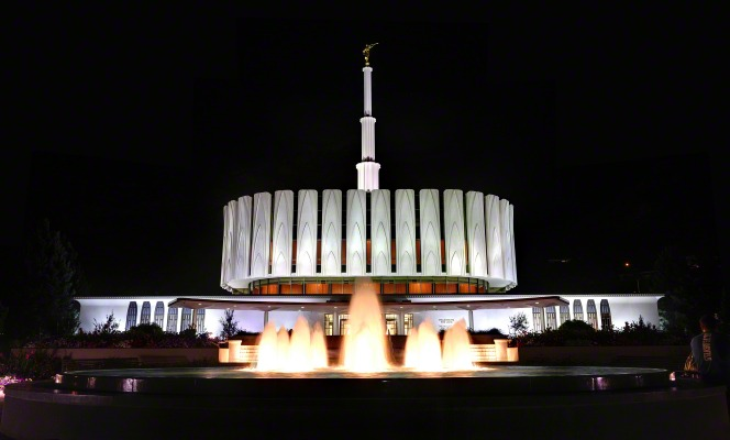 A full front view of the Provo Utah Temple and water fountain at night, both lit up by lights.