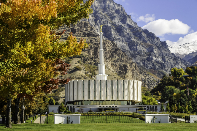 The north side of the Provo Utah Temple, with a view of the grounds around the temple and the mountains behind.