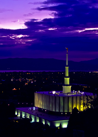 The Provo Utah Temple lit up at night, with a view of the city below, including a partial view of the lake in the background.