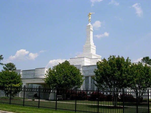 The entire Raleigh North Carolina Temple, with trees and bushes on the grounds within the fence.