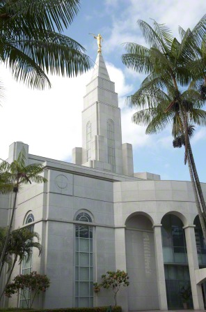 The spire of the Recife Brazil Temple, including a partial view of the entrance to the temple and the trees on the grounds around the temple.