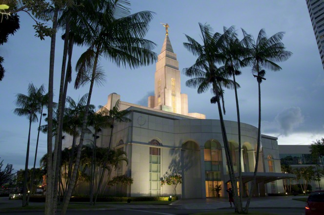 The entire Recife Brazil Temple lit up in the evening, with a view of the trees on the grounds of the temple and a partial view of city buildings nearby.