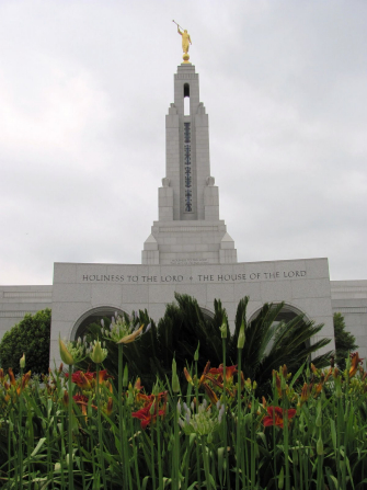 "The spire of the Redlands California Temple, with a partial view of the entrance and the inscription ""Holiness to the Lord: The House of the Lord."" Trees and flowers are in the foreground."