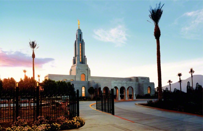 The entire Redlands California Temple in the late evening, with the windows lit up from inside and a view of the fence around the grounds of the temple, including palm trees, bushes, and the road leading to the entrance of the temple.