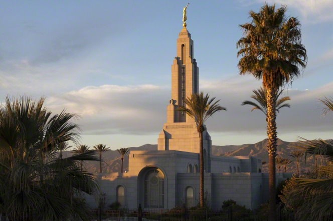 The top of the Redlands California Temple, including a view of some windows and the spire. Trees surround the temple at sunset.
