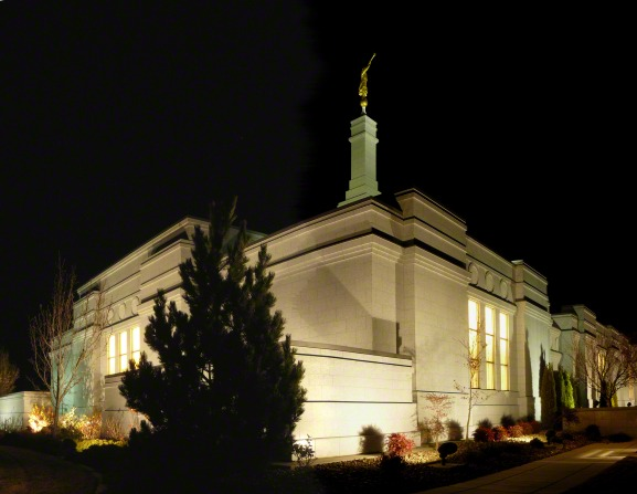 A side view of the Reno Nevada Temple lit up at night, with a partial view of the grounds.