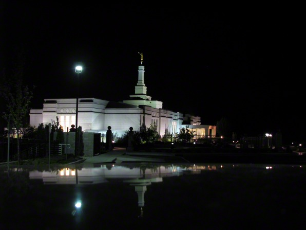 The entire Reno Nevada Temple lit up at night, with a view of the reflecting pond and the grounds around the temple.