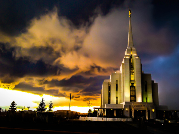 The entire Rexburg Idaho Temple lit up at night, with the sunset in the background.