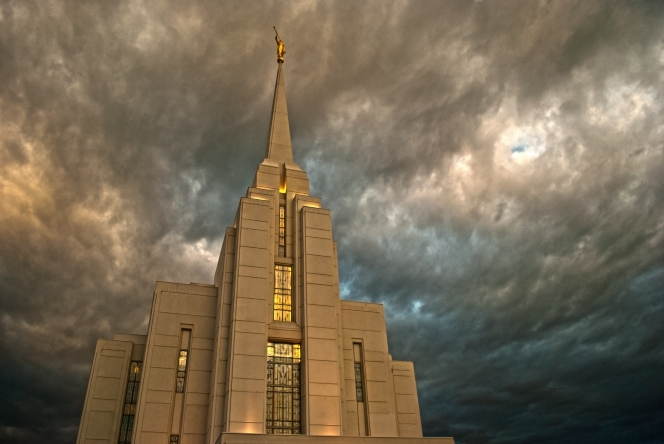 The front of the Rexburg Idaho Temple, with storm clouds above the spire.