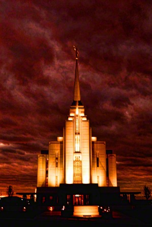 The front of the Rexburg Idaho Temple lit up, with a storm going on around it and storm clouds above.