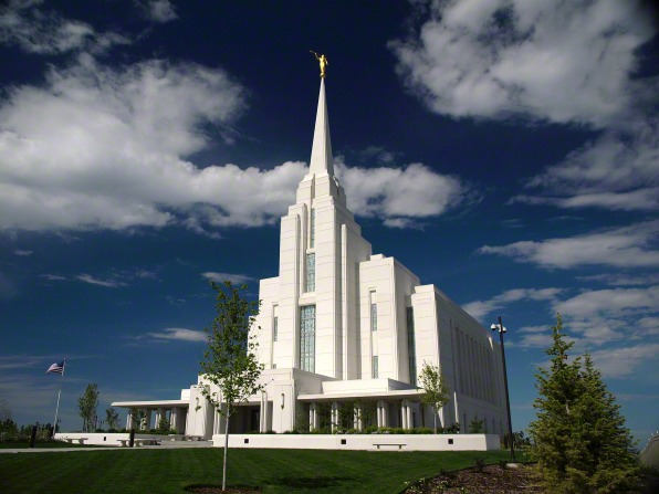 The Rexburg Idaho Temple during the day, with trees on the grounds and a blue sky above.