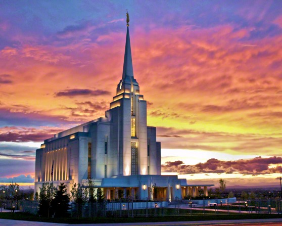 The entire Rexburg Idaho Temple lit up in the late evening, with the sunset in the background and a view of the grounds and valley.