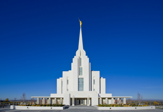 The front of the Rexburg Idaho Temple, including the entrance and grounds on either side, with a view of the valley in the background.