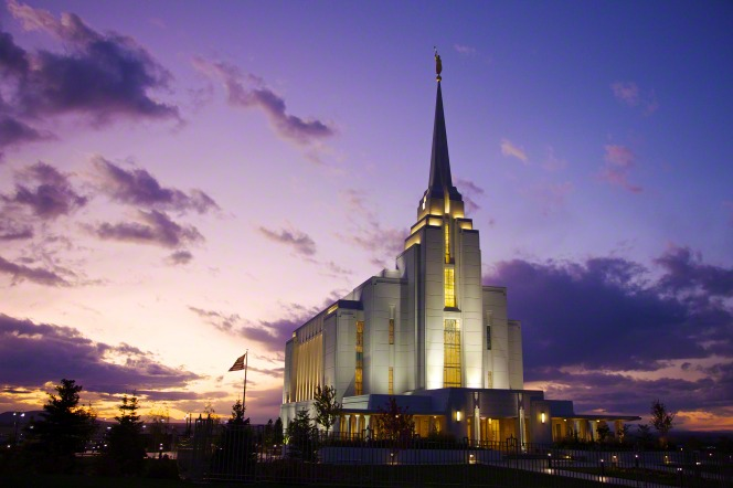 The entire Rexburg Idaho Temple lit up in the late evening, with a view of the grounds around the temple.
