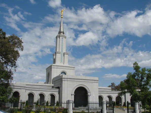 The entrance of the Sacramento California Temple, with a view of the spire and arches on either side of the doors.