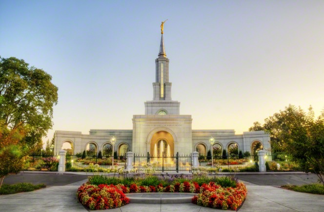 The Sacramento California Temple lit up in the early evening, with its fence, fountains, flowers, and trees.