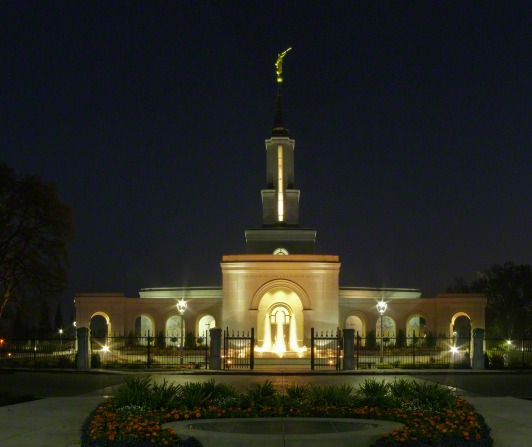 The front of the Sacramento California Temple lit up at night, with a view of the grounds, including the fountain out front, flowers, trees, and the angel Moroni on the spire.