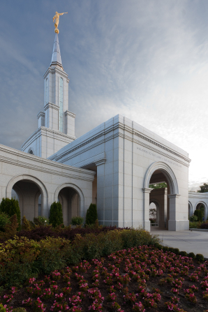 The entrance to the Sacramento California Temple, with a view of the temple spire and flowers on the temple grounds.