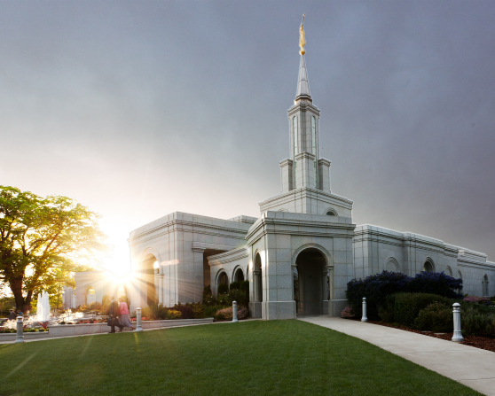 The entire Sacramento California Temple, with the sun setting in the background and a view of the grounds around the temple.