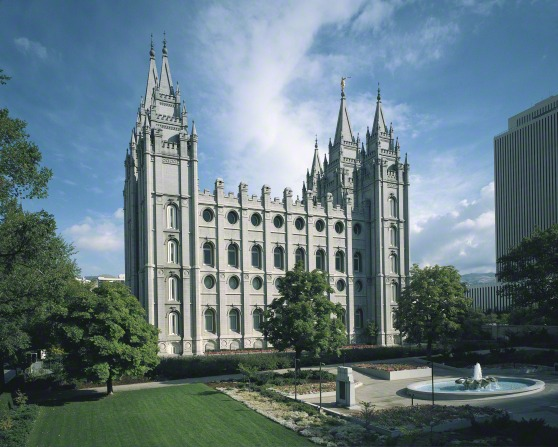A side view of the Salt Lake Temple and grounds, including a fountain and trees.