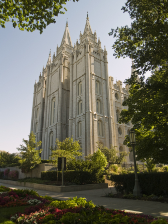 The back of the Salt Lake Temple, with a view of three of the temple spires and the trees on the grounds of the temple.