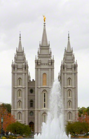 The front of the Salt Lake Temple, with a fountain in the foreground and trees on either side of the temple, changing colors during the fall.
