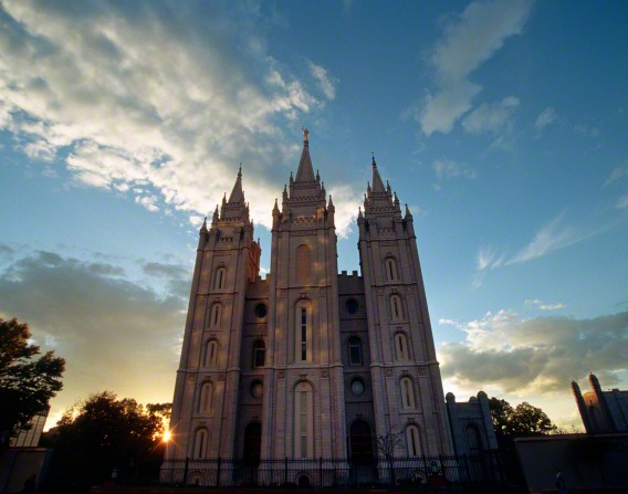The front of the Salt Lake Temple in the evening, with the sun setting behind it and a view of the sky.
