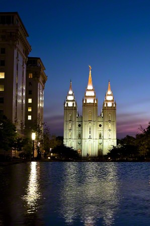 A view of the Salt Lake Temple all lit up at night from the grounds of the temple, with a pond in front.