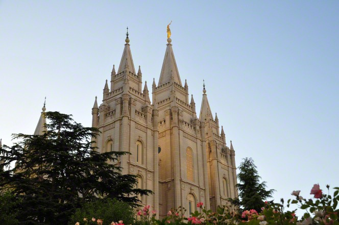 The front three spires of the Salt Lake Temple, rising above the trees and flowers on the grounds of the temple in the evening.