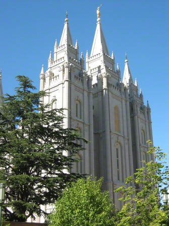 The front three spires of the Salt Lake Temple rising above the trees on the grounds of the temple.