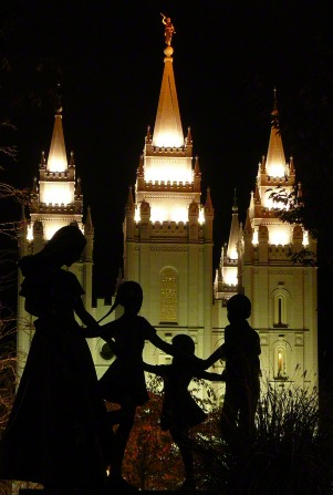 A statue on the grounds of the Salt Lake Temple, silhouetted by the lights from the temple in the background.