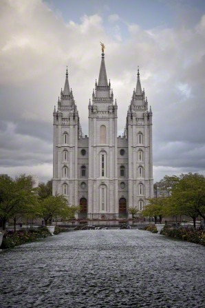 A view of the front of the Salt Lake Temple from the temple grounds. The grounds are lined with trees and covered in snow.
