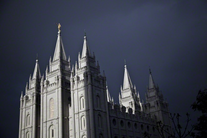 The Salt Lake Temple with a storm overhead. A view of the windows, the angel Moroni, and five of the six spires.