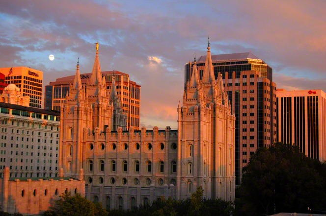 A side view of the entire Salt Lake Temple during sunset and a view of Salt Lake City in the background.