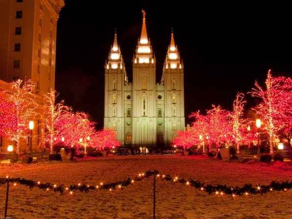 The Salt Lake Temple lit up at night, with trees on the temple grounds covered in Christmas lights, leading up to the front of the temple.