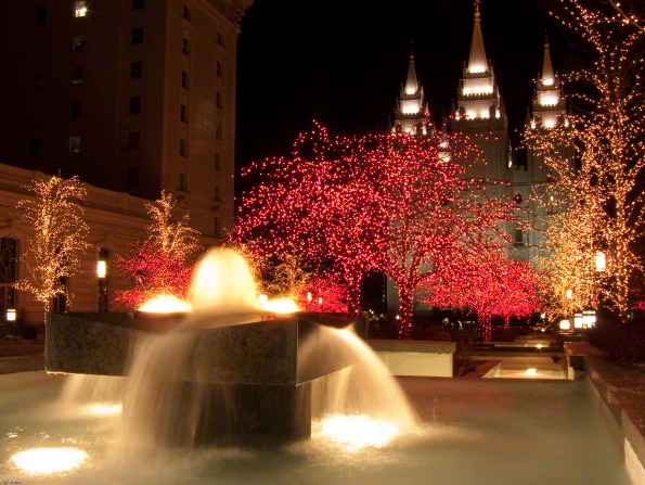 A fountain on the grounds of the Salt Lake Temple, with trees around it covered in Christmas lights and the temple partially viewed in the background.