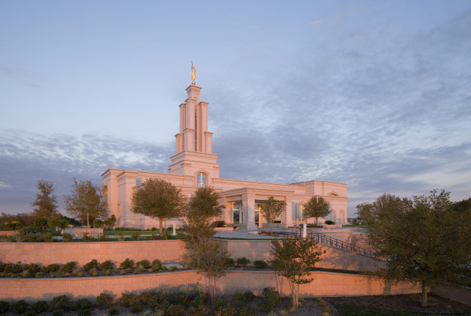 The entire San Antonio Texas Temple in the evening, with the sunset reflecting off of the temple and with a view of the entrance, stairs, and grounds around the temple.