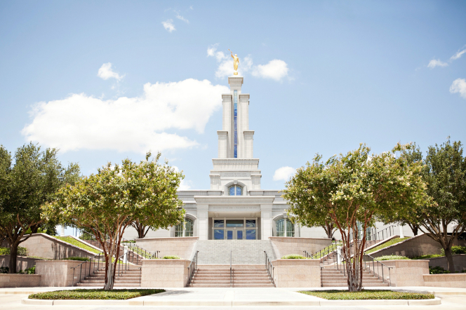 The entrance to the San Antonio Texas Temple, with stairs leading to the doors and a view of the spire, grounds, and trees on either side of the temple.