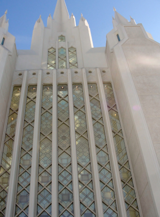 A window of the San Diego California Temple, with a partial view of the spires extending above it.