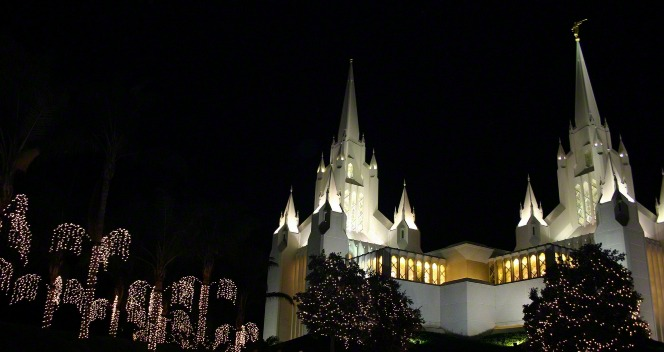 The entire San Diego California Temple lit up at night, with the trees on the temple grounds covered in Christmas lights.
