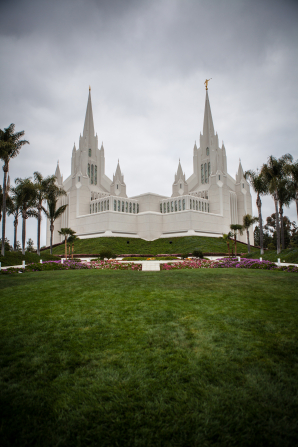 The entire San Diego California Temple, with a view of the grounds and palm trees on either side of the temple.
