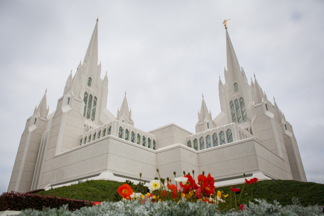 A side view of the entire San Diego California Temple, including the spires and the grounds, with flowers blooming on the grounds.