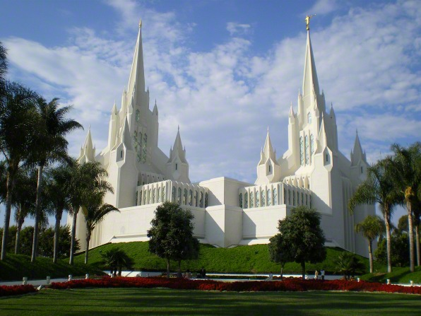 The entire San Diego California Temple, with a view of the grounds, lined with trees, flowers, and bushes.
