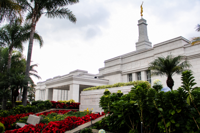 The entrance to the San José Costa Rica Temple, with a view of the temple name sign and the grounds around the temple. Trees, flowers, and bushes line the grounds.