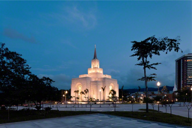 The San Salvador El Salvador Temple lit up at night, with the surrounding grounds and a partial view of the parking lot and the city in the background.