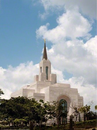 A partial view of the San Salvador El Salvador Temple, with a view of some windows, the spire, and trees on the grounds around the temple.