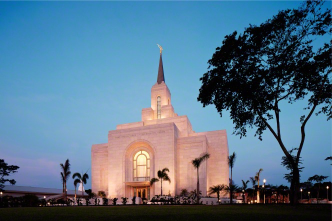 The entire San Salvador El Salvador Temple in the evening, with windows lit from inside and the temple lit on the outside, surrounded by trees on the temple grounds.