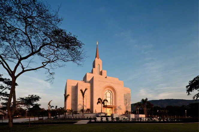 The entire San Salvador El Salvador Temple in the evening, including a view of the windows lit from inside, the grounds, and the trees surrounding the temple.